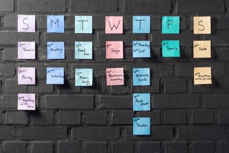 Photo pour Notes autocollantes colorées sur mur de briques noires - image libre de droit