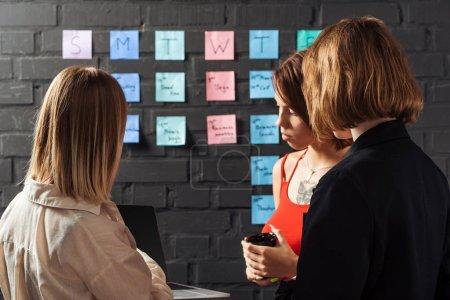 Photo pour Femmes debout près de notes autocollantes colorées sur le mur de briques noires, regardant ordinateur portable - image libre de droit