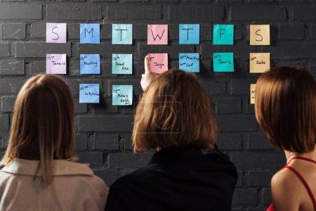 Photo pour Vue arrière de trois femmes debout près de notes autocollantes colorées et pointant vers le mur de briques noires - image libre de droit