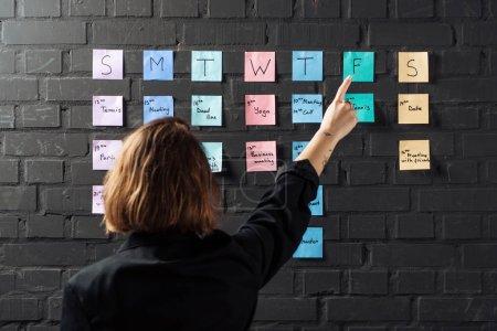 Photo pour Vue arrière de la femme pointant du doigt des notes autocollantes colorées sur un mur de briques noires - image libre de droit