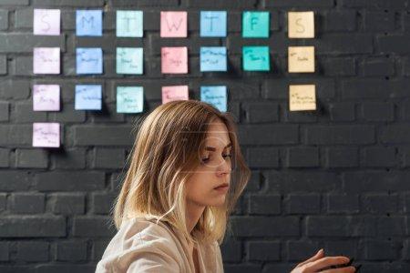 Photo pour Vue latérale de la femme debout près de notes autocollantes colorées sur le mur de briques noires, regardant loin - image libre de droit
