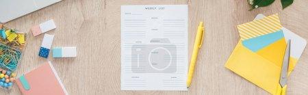 Photo pour Vue panoramique de la liste hebdomadaire et de la papeterie sur table en bois - image libre de droit