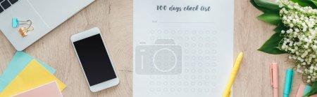 Foto de Vista panorámica de papelería, lista de verificación de 100 días, flores y teléfono inteligente en la mesa de madera - Imagen libre de derechos