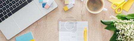 Photo pour Vue panoramique du planificateur mensuel, fleurs, ordinateur portable et tasse à café sur table en bois - image libre de droit