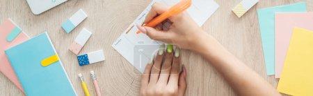 Photo pour Vue recadrée de femme écrivant des notes à faire liste, assis derrière la table en bois avec papeterie - image libre de droit