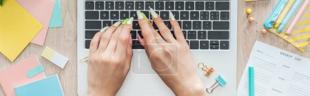 Photo pour Vue recadrée de femme tapant sur le clavier d'ordinateur portatif, s'asseyant derrière la table en bois avec la papeterie et la liste hebdomadaire - image libre de droit