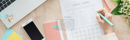 Photo for Cropped view of woman writing notes at monthly planner, sitting behind wooden table with stationery, notepad and smartphone - Royalty Free Image