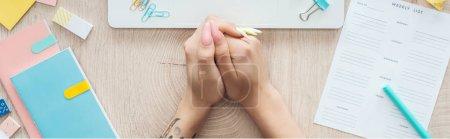 Photo pour Vue recadrée de femme tenant la main sur une table en bois avec liste hebdomadaire et papeterie - image libre de droit