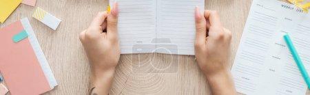 Photo pour Vue recadrée de la femme tenant un bloc-notes dans les mains sur une table en bois avec liste hebdomadaire et papeterie - image libre de droit