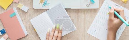 Photo pour Vue recadrée de la femme prenant des notes dans la liste hebdomadaire, assis derrière la table en bois avec bloc-notes et papeterie - image libre de droit