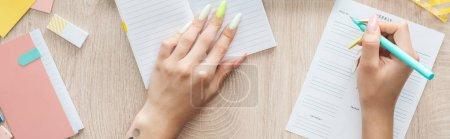 Photo pour Vue recadrée de femme écrivant en liste hebdomadaire, assise derrière une table en bois avec bloc-notes et papeterie - image libre de droit