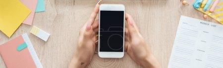 Photo pour Vue recadrée de la femme tenant smartphone sur une table en bois avec ordinateur portable, liste hebdomadaire et papeterie - image libre de droit