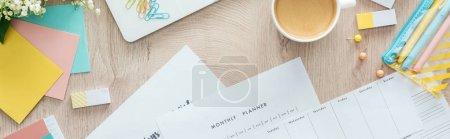 Photo pour Vue panoramique du café dans la tasse blanche, des planificateurs et des fleurs avec la papeterie sur la table en bois - image libre de droit