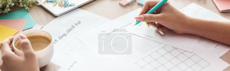 Photo for Cropped view of woman holding pen and coffee cup in hands, writing notes in planners, sitting behind wooden table with flowers and stationery - Royalty Free Image