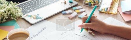 Photo pour Vue recadrée d'une femme tenant un stylo à la main, écrivant des notes dans des planificateurs, assise derrière une table en bois avec des fleurs et de la papeterie - image libre de droit