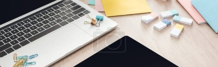 Photo for Panoramic view of laptop, digital tablet and stationery on wooden table - Royalty Free Image