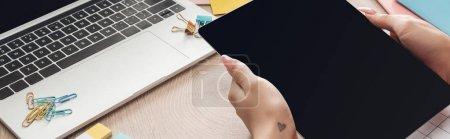Photo pour Vue recadrée de la femme tenant tablette numérique dans les mains sur une table en bois avec ordinateur portable, planificateurs et papeterie - image libre de droit