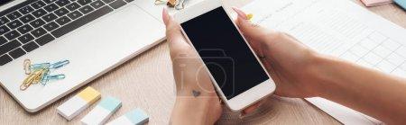 Photo pour Vue recadrée de femme retenant le smartphone dans des mains au-dessus de la table en bois avec l'ordinateur portatif, les planificateurs et la papeterie - image libre de droit