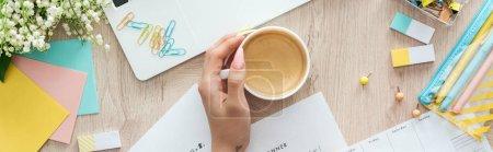 Photo pour Vue recadrée de tasse de fixation de femme avec le café sur la table en bois avec l'ordinateur portatif et la papeterie - image libre de droit