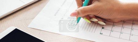 Photo pour Vue recadrée de femme retenant le stylo vert au-dessus du planificateur avec des notes - image libre de droit