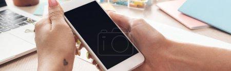 Photo pour Vue recadrée de femme retenant le smartphone dans des mains au-dessus de la table en bois avec l'ordinateur portatif et la papeterie - image libre de droit