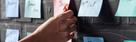 Photo for Cropped view of woman attach colorful sticker pads with notes on black brick wall - Royalty Free Image