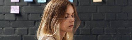 Photo pour Femme regardant loin, restant près du mur de briques avec les garnitures colorées d'autocollant - image libre de droit