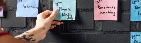 Photo pour Vue recadrée de femme tenant dans la main tampon autocollant coloré avec des notes - image libre de droit