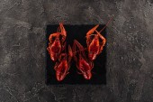 """Постер, картина, фотообои """"top view of black plate with red lobsters on grey textured surface"""""""