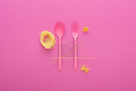 Photo pour Cuillère et fourchette en plastique rose à proximité de différents types de pâtes isolées sur rose - image libre de droit
