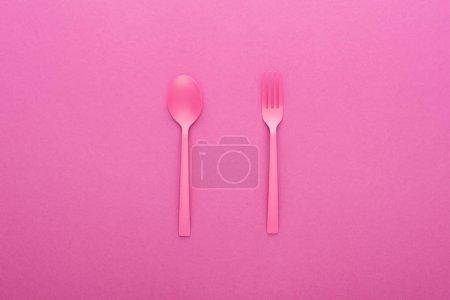 Photo pour Cuillère et fourchette en plastique rose isolées sur rose - image libre de droit