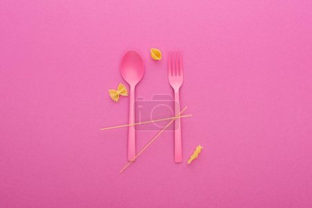 Photo for Pink plastic spoon and fork and four different kinds of pasta isolated on pink - Royalty Free Image