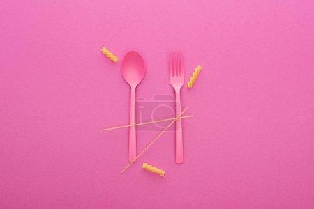 Photo pour Cuillère et fourchette en plastique rose et deux types différents de pâtes isolées sur rose - image libre de droit