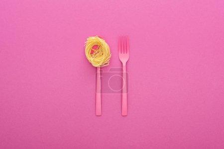 Photo pour Fourchette et pâtes en plastique rose sur cuillère rose sur fond rose - image libre de droit