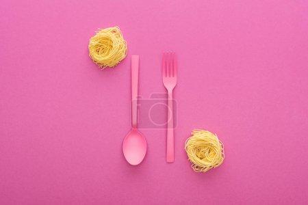Photo pour Fourchette et cuillère en plastique rose à l'envers près des pâtes vermicelles sur fond rose - image libre de droit