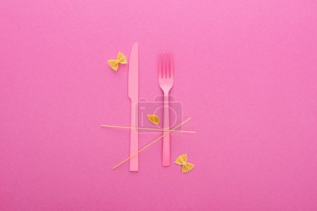 Photo for Pink plastic knife and fork, spaghetti, uncooked farfalle pasta and shell macaroni isolated on pink - Royalty Free Image
