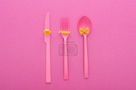 Photo pour Vue de dessus de différents types de pâtes sur des couverts en plastique rose isolés sur rose - image libre de droit