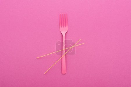 Photo for Top view of pink plastic fork and spaghetti isolated on pink - Royalty Free Image