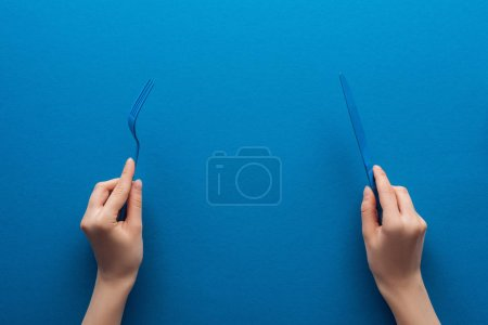 cropped view of woman holding blue plastic fork and knife on blue background