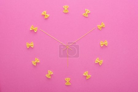 Photo for Top view of clock concept with uncooked farfalle pasta and spaghetti isolated on pink - Royalty Free Image