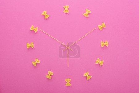 Photo pour Vue du haut du concept d'horloge avec les pâtes de farfalle non cuites et les spaghettis isolés sur le rose - image libre de droit