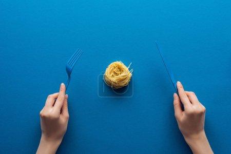 Photo pour Vue recadrée d'une femme tenant une fourchette et un couteau en plastique bleu avec des pâtes vermicelles au milieu sur fond bleu - image libre de droit