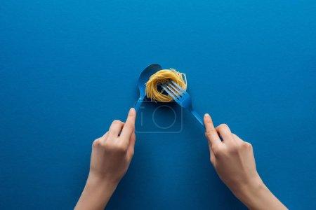 Photo pour Vue recadrée de la femme tenant une cuillère bleue et prenant des pâtes vermicelles avec fourchette isolée sur bleu - image libre de droit
