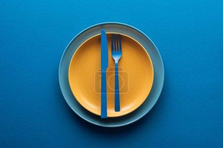 Draufsicht auf blaues Plastikmesser und -gabel auf gelbem Teller über einem anderen Teller auf blauem Hintergrund