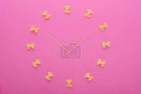 Photo for Top view of clock concept with uncooked farfalle pasta and spaghetti in middle isolated on pink - Royalty Free Image