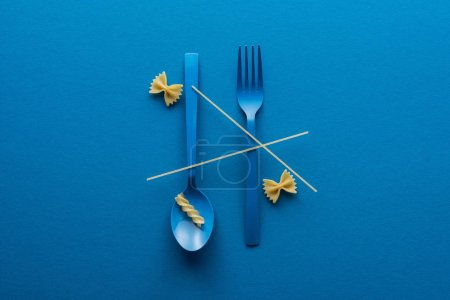 Photo pour Vue supérieure de spaghetti sur la cuillère en plastique bleue à l'envers et à la fourchette près de deux genres de pâtes sur le fond bleu - image libre de droit