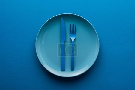 Photo for Blue plastic knife and fork on plate on blue background - Royalty Free Image