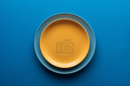 Photo for Top view of blue plate under yellow one on blue background - Royalty Free Image