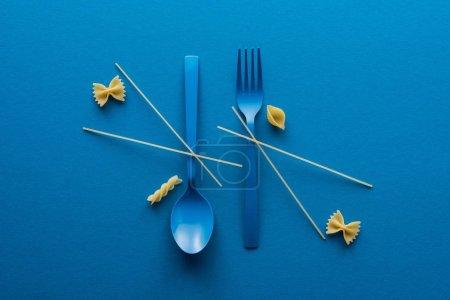Photo pour Couche plate de spaghettis sur une cuillère en plastique bleu à l'envers et fourchette à proximité de différents types de pâtes non cuites sur fond bleu - image libre de droit