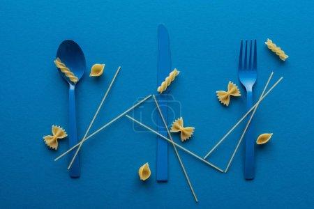 Photo pour Couverts en plastique bleu avec spaghettis non cuits et différents types de pâtes sur fond bleu - image libre de droit